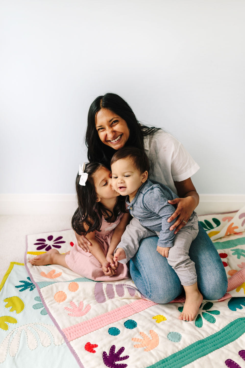 An adorable family photoshoot with a handmade quilt. This Bohemian Garden quilt pattern was inspired by the paper cut-outs of Henri Matisse