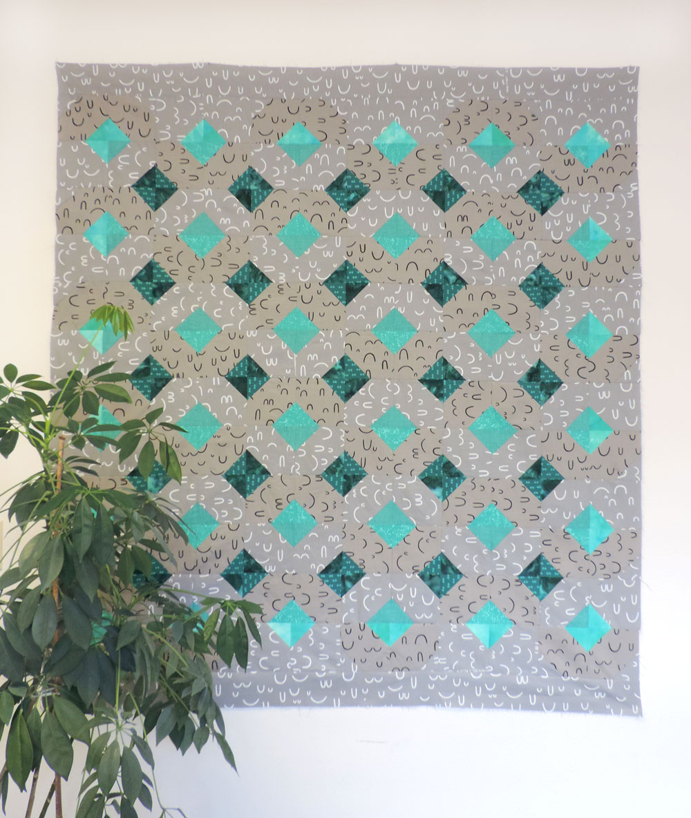This gray and teal Arroyo quilt is subtle and shows how different the Glitter and Glow pattern can look based on the fabrics you choose.