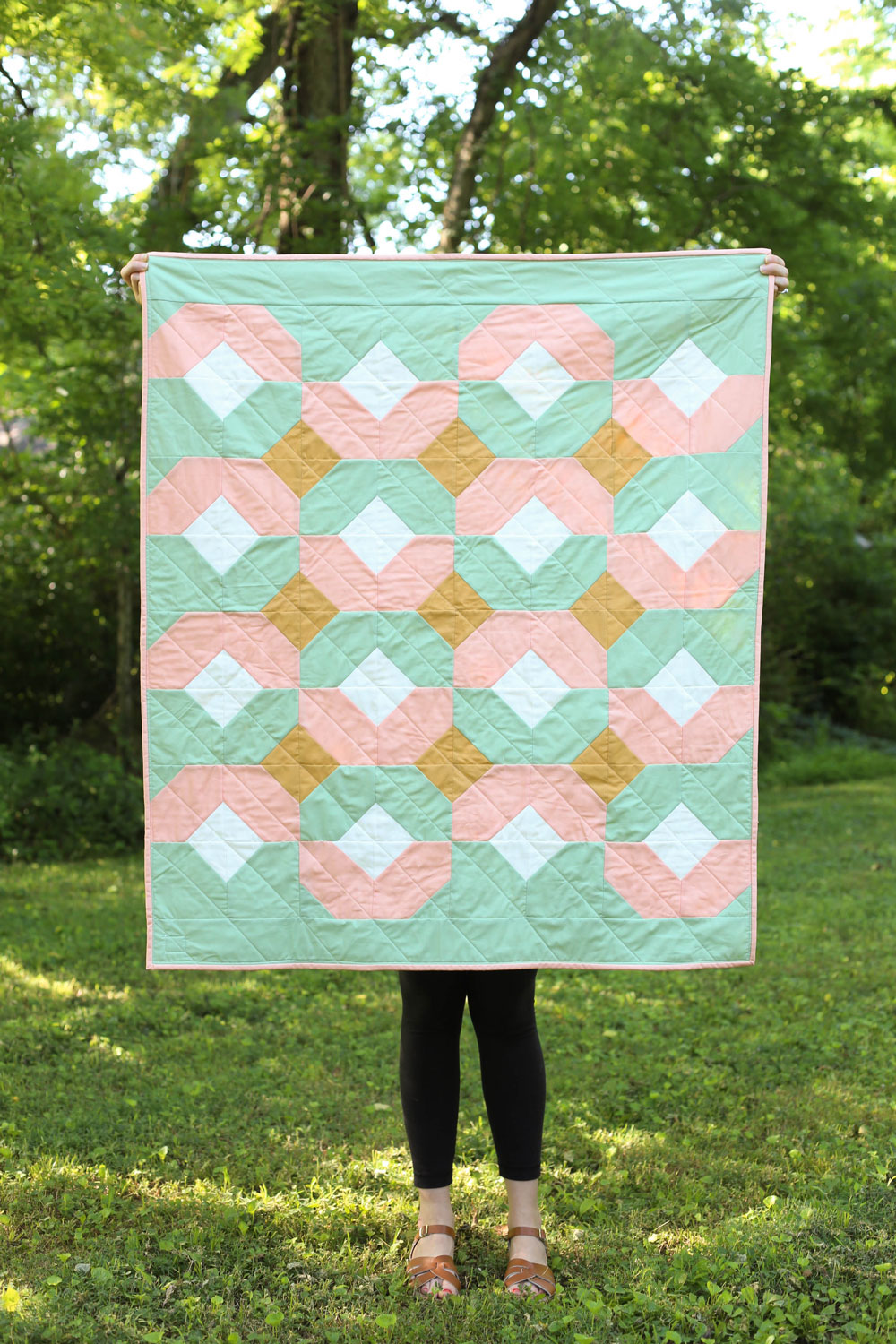 This pink and mint green baby quilt is perfect for sping! The Glitter and Glow quilt pattern comes in king through baby quilt sizes and is beginner friendly.