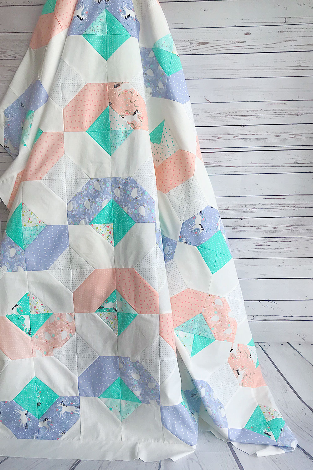 This Peach and Periwinkle Glitter quilt is so cute! Featuring ponies, swans, and sweet little flowers.