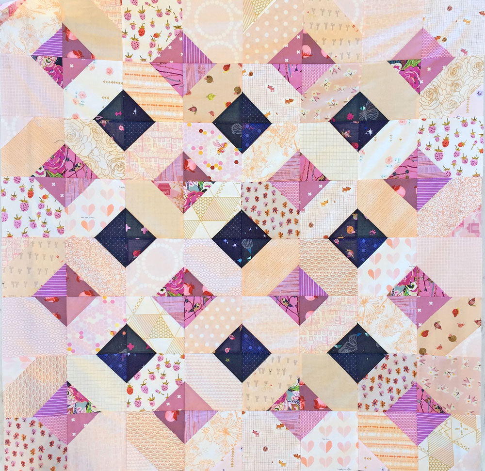 The Glitter and Glow quilt pattern can be a great way to use up scraps! Just like this sweet and scrappy purple baby quilt.