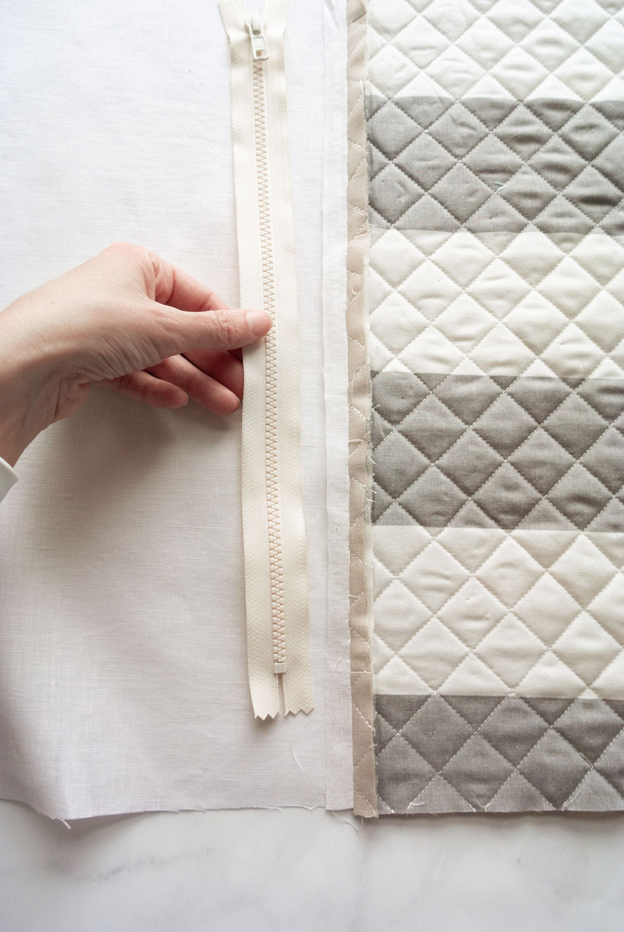 Elegant Quilted Pillow DIY! Sew a quilted zipper pillow with this step by step tutorial. I'll walk you through how to baste and quilt your pillow top, sew a zipper, and finish the pillow beautifully!