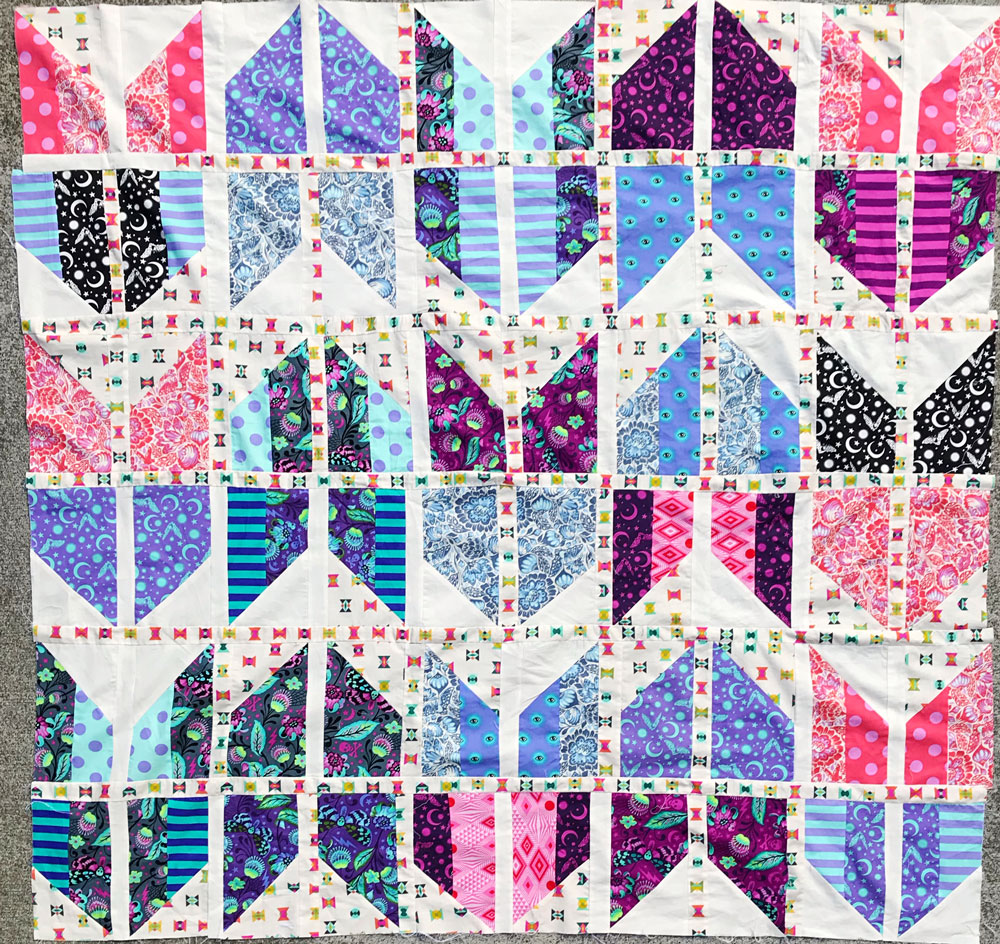 The Tail Feather quilt pattern is a bold, modern design that is fat quarter friendly. It comes in baby, throw, twin, and queen sizes. Beginner friendly! SUZY QUILTS #quiltpattern #modernquilt