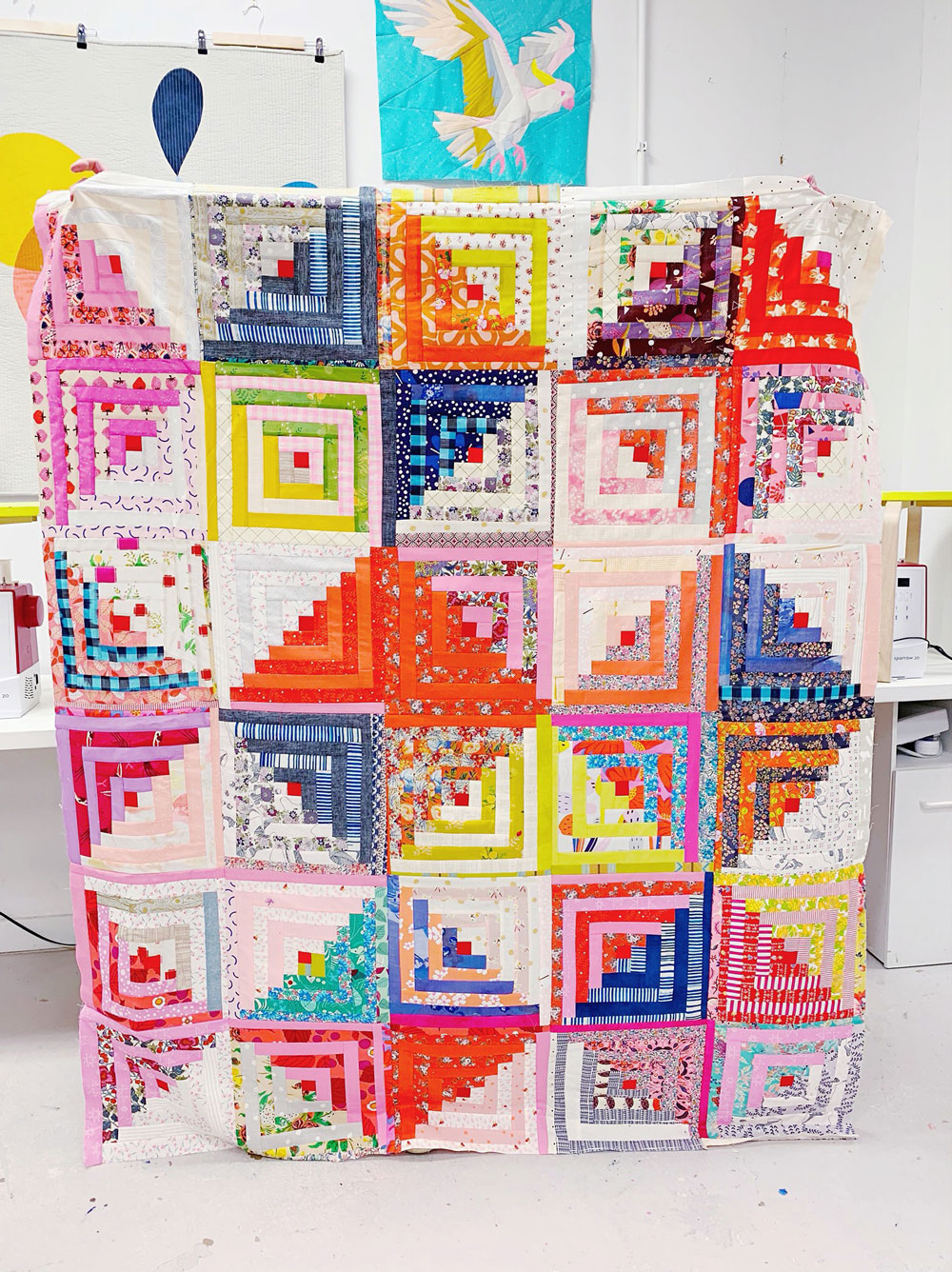 Annabel Wrigley is the founder of Little Pincushion Studio – a creative place that teaches sewing workshops to children as well as adults! Annabel is known for her colorful doodle quilts and bright fabric designs. suzyquilts.com #logcabinquilt #rainbowquilt