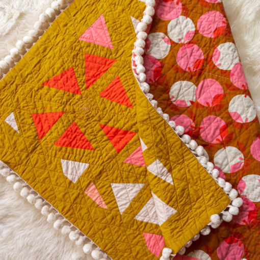 The perfect flower quilt pattern to add some cute pom poms! The Perennial quilt pattern looks like wildflowers growing in a meadow – so use your scraps! Fat quarter and fat eighth friendly plus video tutorials! suzyquilts.com #PomPomQuilt