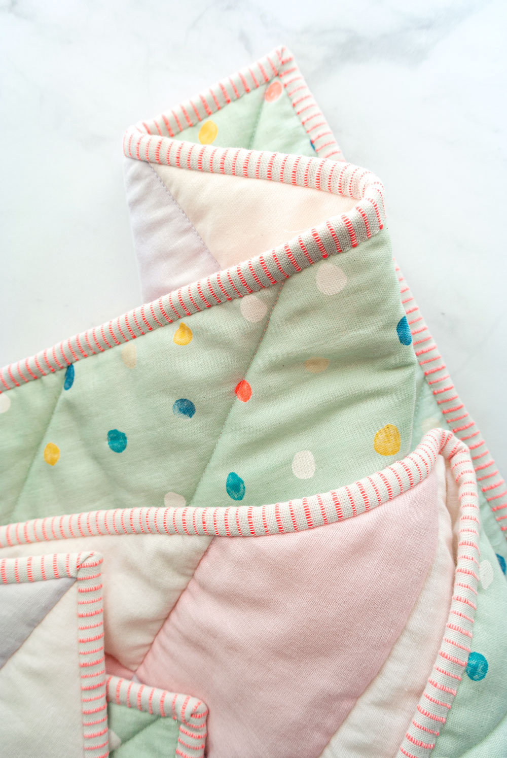 How to make the softest baby quilt in the world! The answer is to quilt with double gauze and wool batting – a sewing tutorial on how to do both! suzyquilts.com #babyquiltpattern #quiltbinding