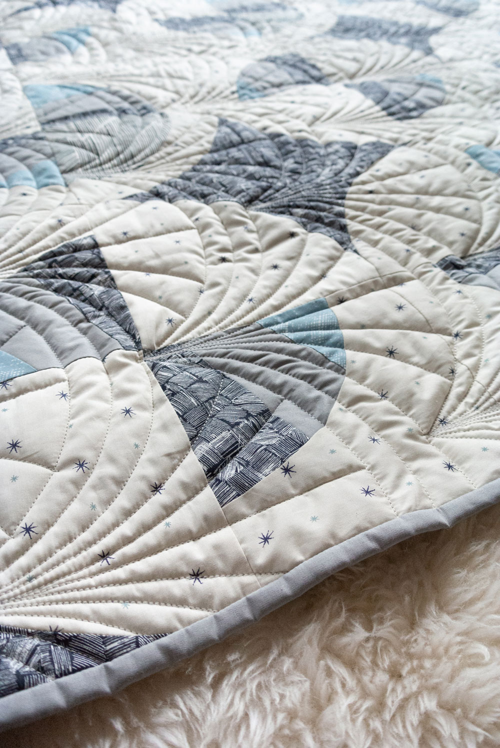 This Great Gatsby inspired Modern Fans quilt kit uses icy blues, grays and metallic silver fabric to bring elegance and pizzazz to a cozy quilt. suzyquilts.com #quiltpattern #quilt #modernfansquilt