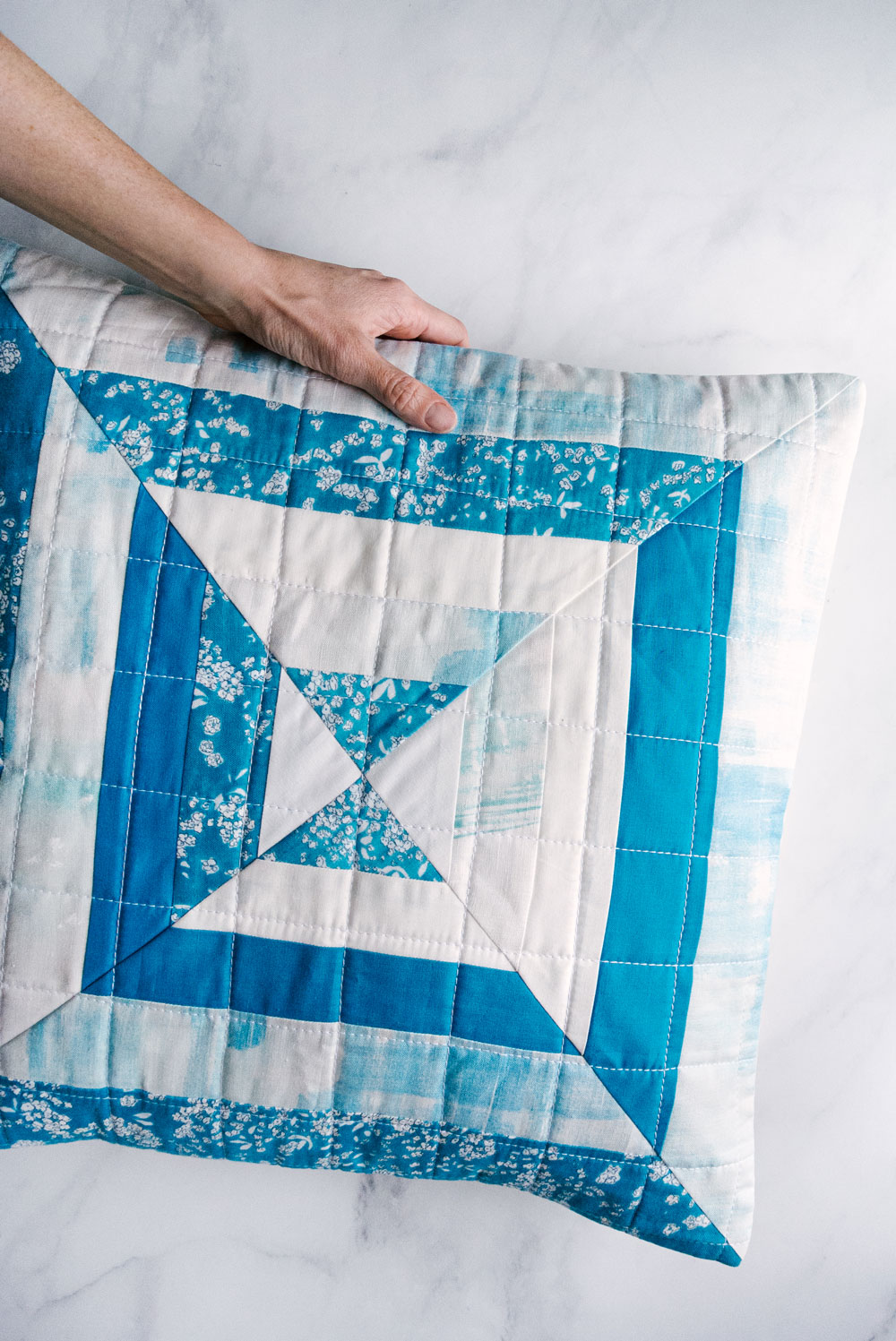 The Reflections pillow is a very fast project that is perfect for using scraps of fabric! This modern quilt pattern includes instructions for an 18-inch pillow and a 30-inch wall hanging. suzyquilts.com #pillowpattern