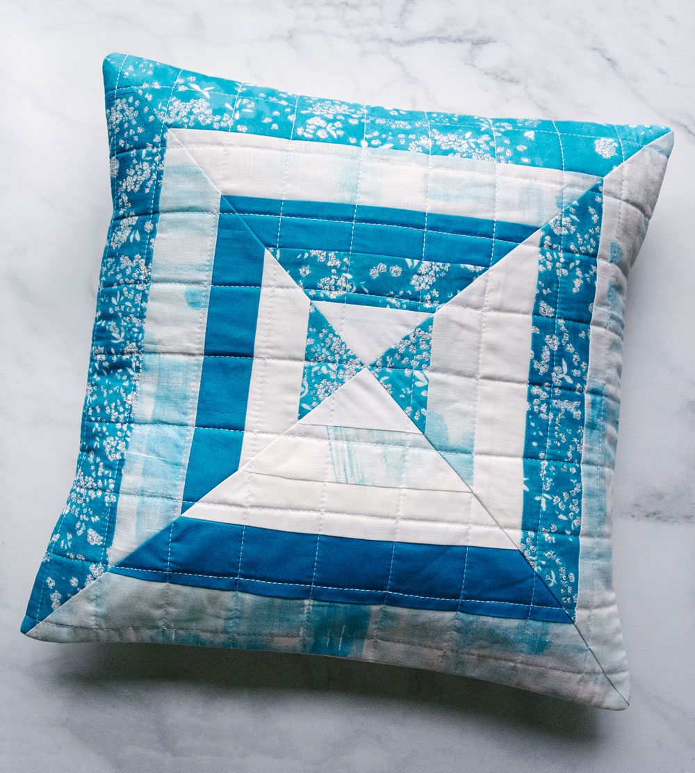The Reflections pillow is a very fast project that is perfect for using scraps of fabric! This modern quilt pattern includes instructions for an 18-inch pillow and a 30-inch wall hanging. suzyquilts.com #quiltedpillow