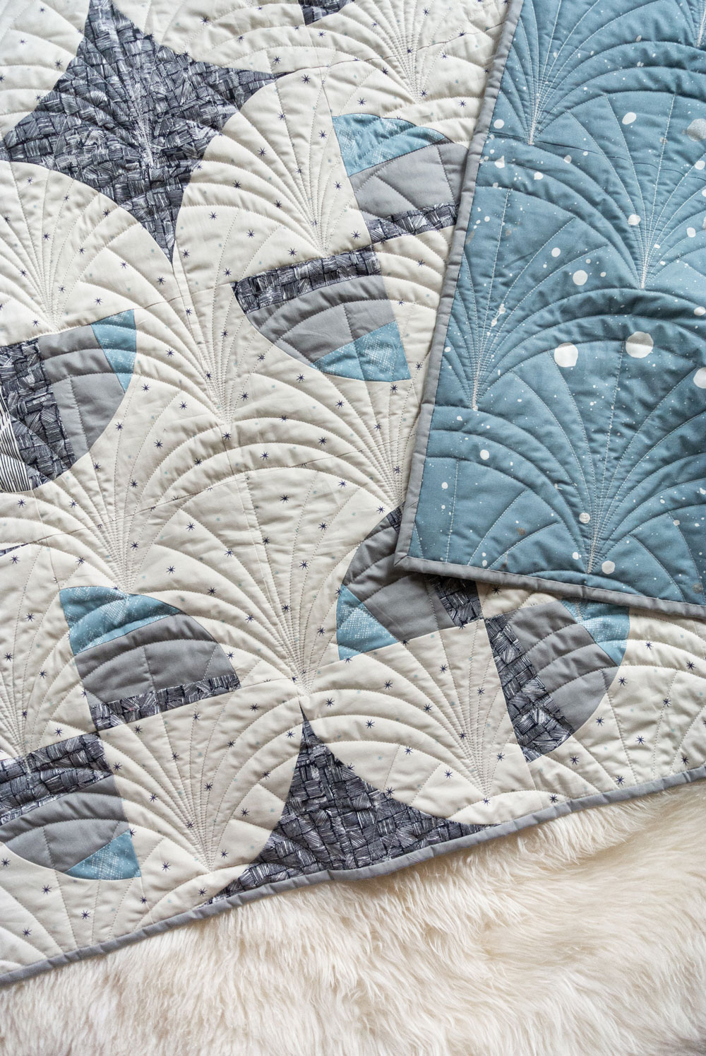 This Great Gatsby inspired Modern Fans quilt kit uses icy blues, grays and metallic silver fabric to bring elegance and pizzazz to a cozy quilt. suzyquilts.com #quiltpattern #artdecoquilt