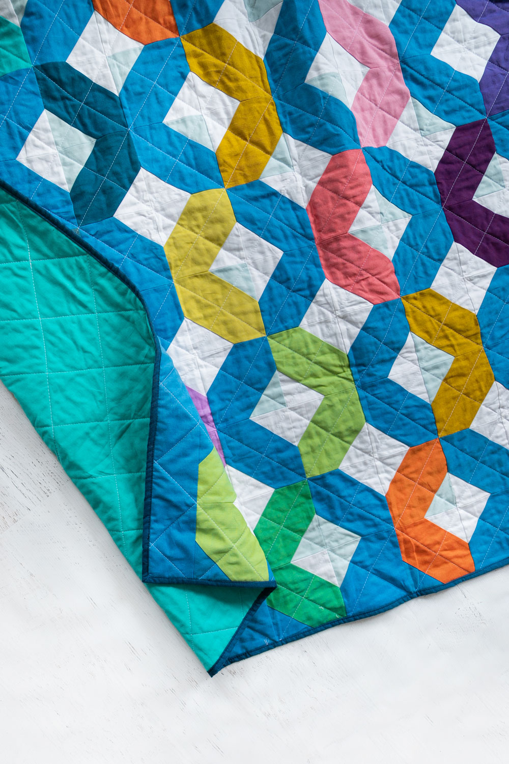 Make a Rainbow Quilt using this simple alteration to the Glitter & Glow quilt pattern. This is fat quarter friendly and great for newbie quilters and beginners. suzyquilts.com #rainbowquiltpattern