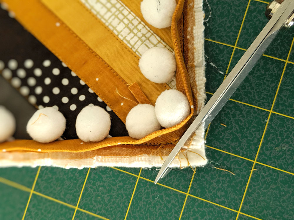 This tutorial will show you step by step how to sew pom pom trim to a quilt. Make your next quilt extra special with this easy sewing tutorial | suzyquilts.com #sewingtutorial #pompomDIY