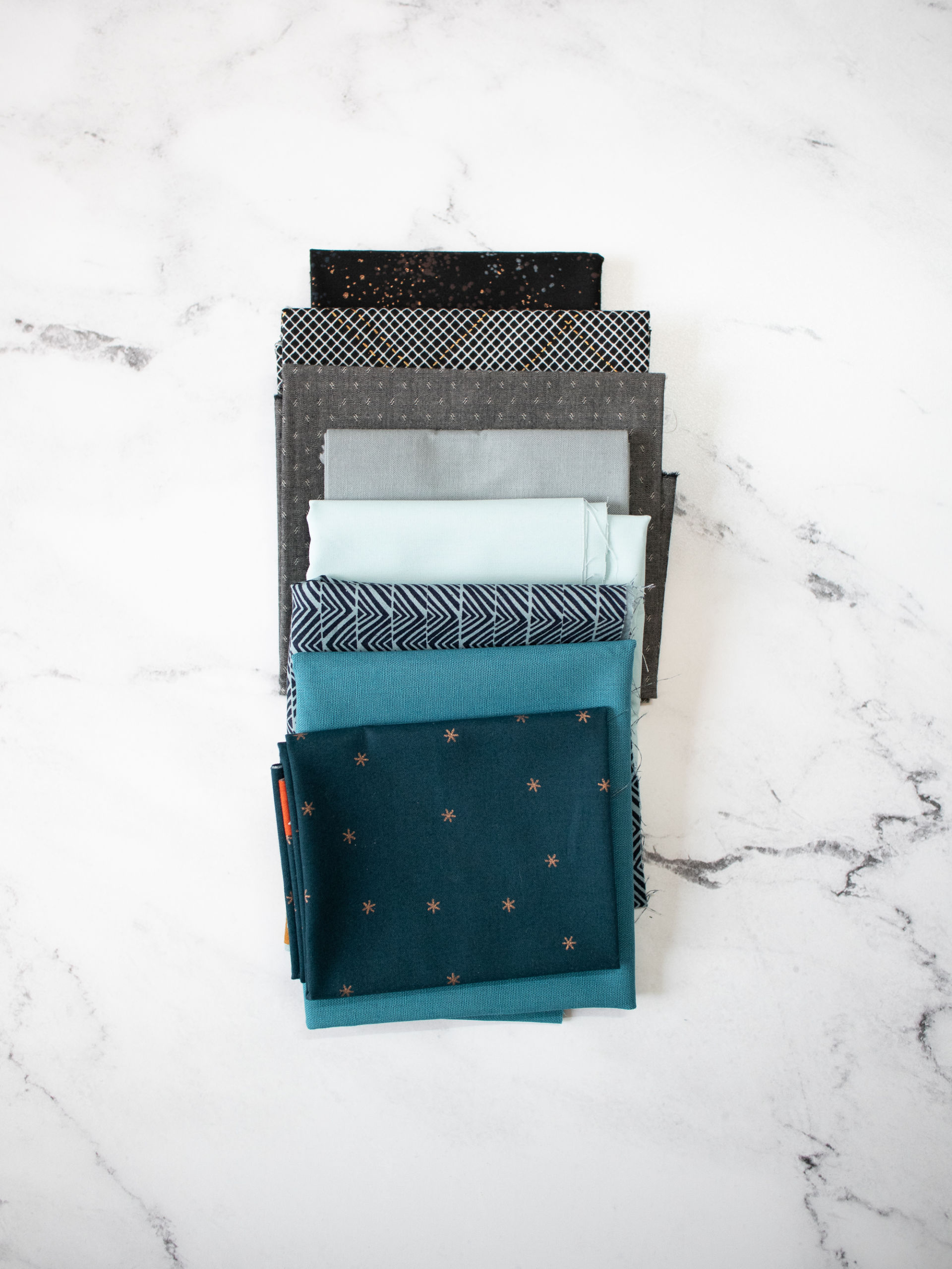 The ultimate guide to folding fabric of different sizes to neatly organize your fabric stash. Step by step photos and instructions show you how to fold fat quarters, half yards, and yardage so you can get started on cleaning your sewing studio. suzyquilts.com #fabricorganization #sewing