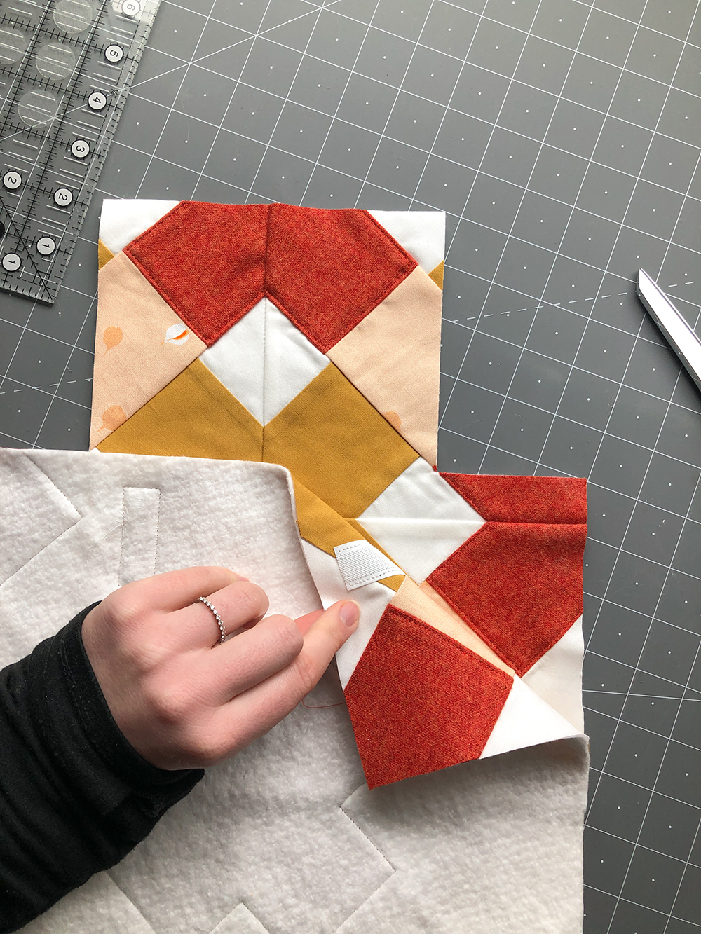 """Place the 4"""" loop-side pieces of velcro on the flap of your lining fabric, 0.5"""" from each edge of the flap. Stitch around the edge of the velcro to secure. Repeat for both pieces of loop-side velcro."""
